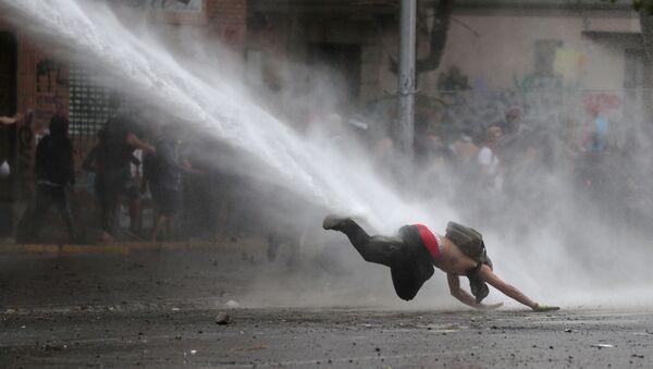 Un manifestante cae al suelo por un tanque de agua durante las protestas en Chile (archivo) - Sputnik Mundo