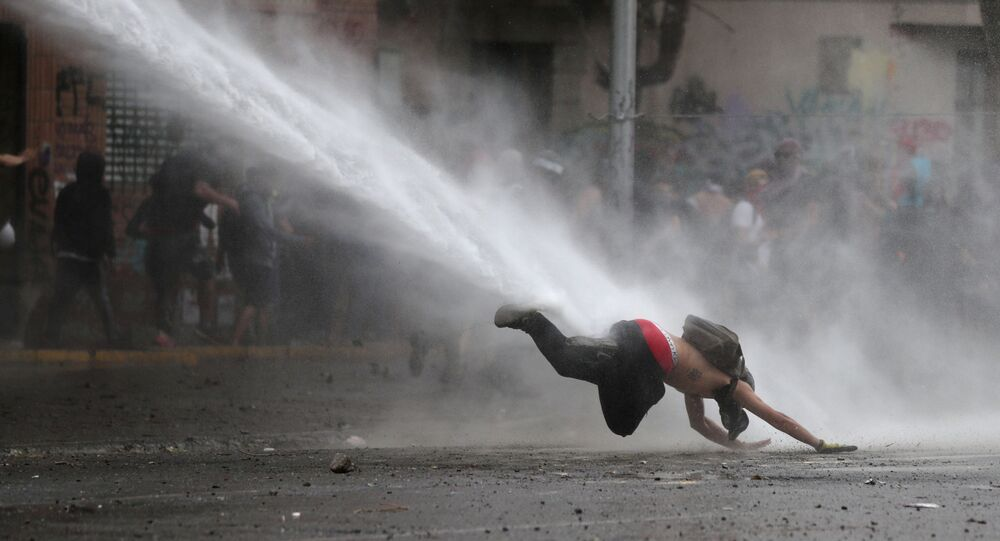 Una manifestante cae al piso por un tanque de agua durante las protestas en Chile