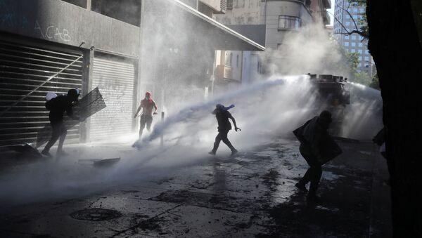 Carabineros dispersando una marcha en Santiago, Chile - Sputnik Mundo