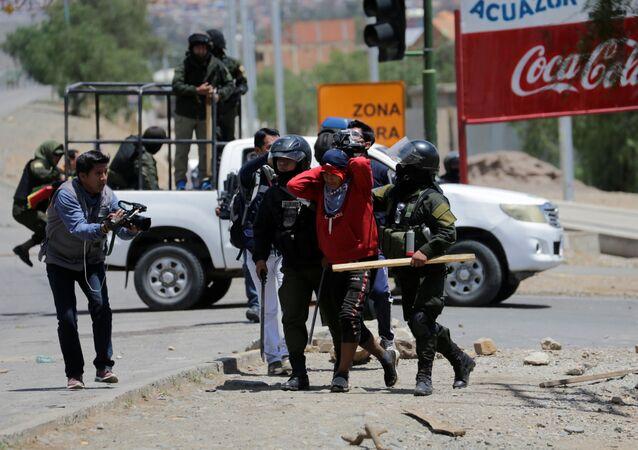 Policía deteniendo a un cocalero durante las protestas en Cochabamba, Bolivia