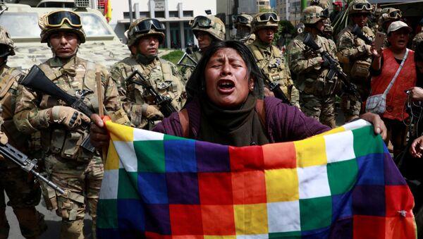 Un manifestante con una bandera de Wiphala frente a miembros de las fuerzas de seguridad durante los enfrentamientos entre partidarios del expresidente boliviano, Evo Morales, y las fuerzas de seguridad en La Paz (Bolivia). - Sputnik Mundo