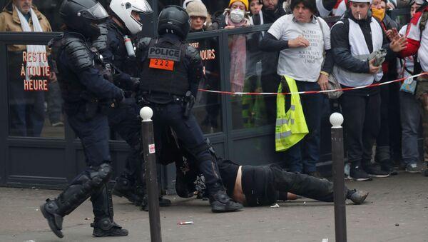 Policía arrestando a un manifestante durante las manifestaciones de los chalecos amarillos en París, Francia - Sputnik Mundo