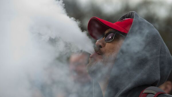 Un hombre fumando de un cigarrillo electrónico - Sputnik Mundo