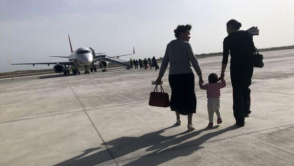 Una familia de uigures en el aeropuerto chino de Kuqa - Sputnik Mundo