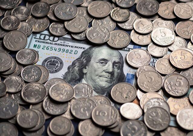 Un billete de cien dólares estadounidenses y monedas de cinco kópeks rusos