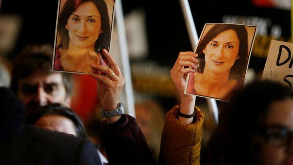 La gente sostiene las fotos de la periodista Daphne Caruana Galizia - Sputnik Mundo