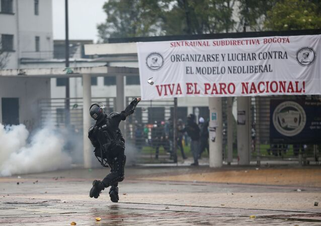 Un policía arroja una bomba de gas a manifestantes durante el paro nacional del 21 de noviembre de 2019 en Bogotá
