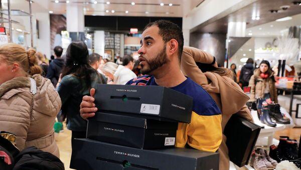 Работник в Мэйси несет коробки для покупателей во время Черную пятницы, Нью-Йорк - Sputnik Mundo
