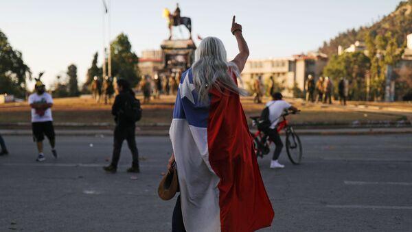 Un manifestante con la bandera de Chile durante las protestas - Sputnik Mundo