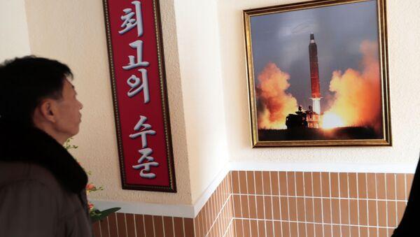 Un hombre mira la foto del lanzamiento de un misil norcoreano - Sputnik Mundo