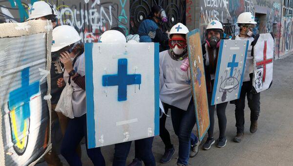 Paramédicos se protegen durante las manifestaciones de protesta en Chile - Sputnik Mundo