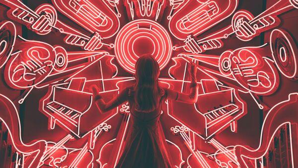 Una mujer delante de un panel con instrumentos musicales - Sputnik Mundo