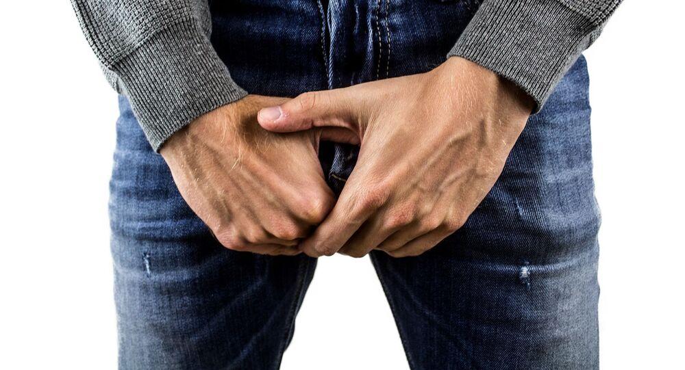 Un hombre con las manos sobre su entrepierna
