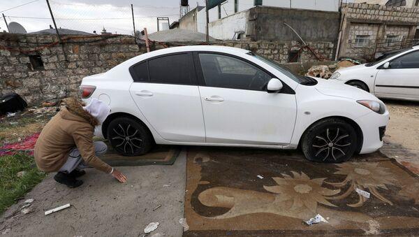 Un palestino examina su coche con los neumáticos rajados en Jerusalén Este - Sputnik Mundo
