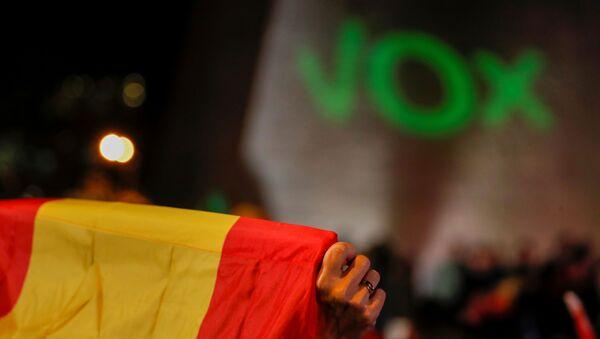 La bandera de España con el letrero de Vox al fondo - Sputnik Mundo
