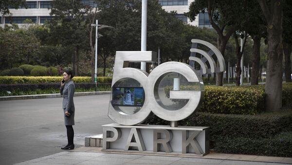 Una empleada de Huawei habla por teléfono cerca de un monumento a la tecnología 5G - Sputnik Mundo