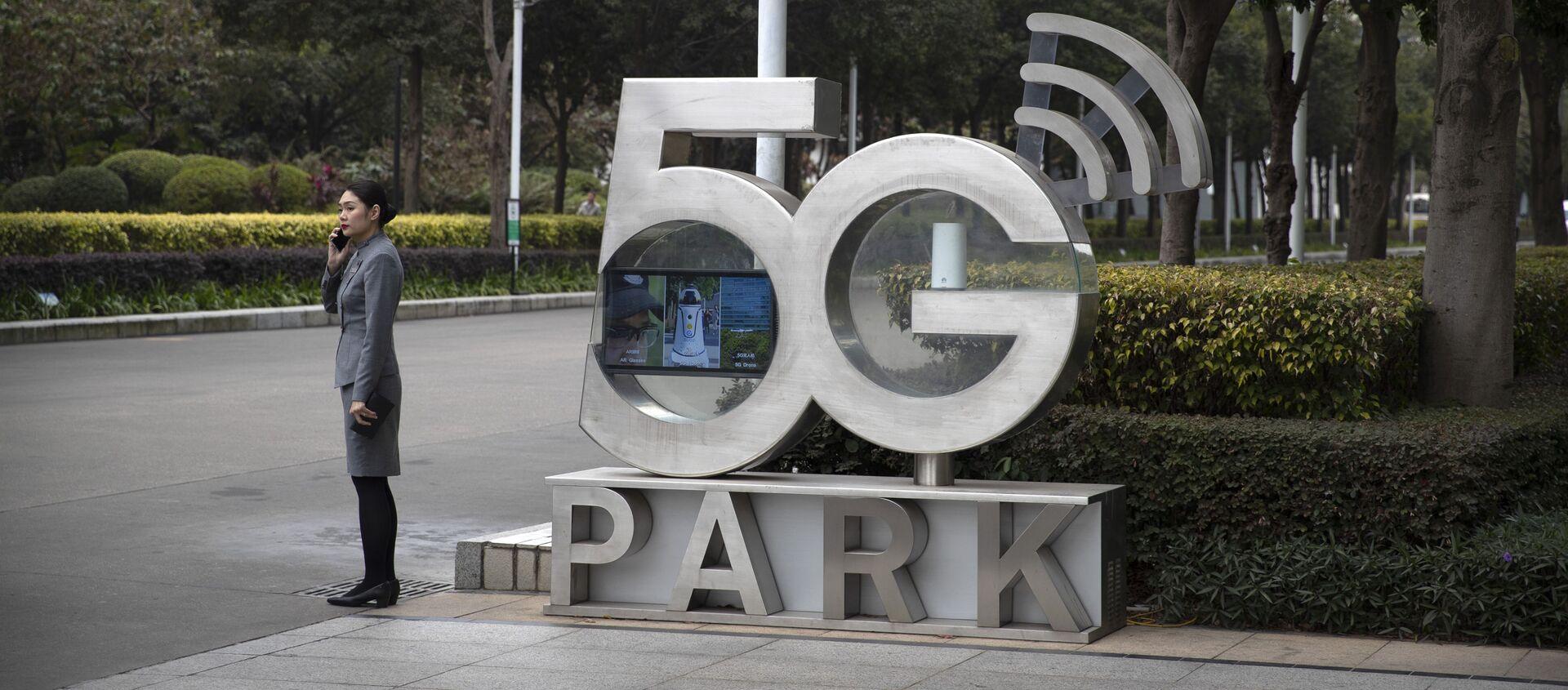 Una empleada de Huawei habla por teléfono cerca de un monumento a la tecnología 5G - Sputnik Mundo, 1920, 06.04.2020