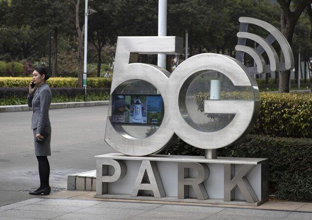 Una empleada de Huawei habla por teléfono cerca de un monumento a la tecnología 5G