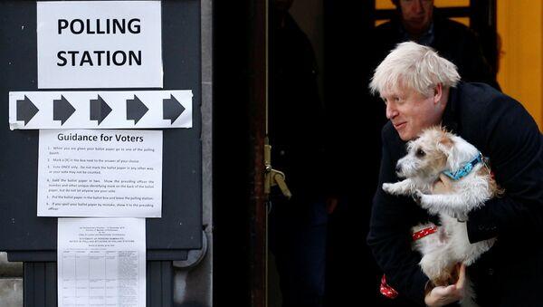 El primer ministro del reino Unido, Boris Johnson, sale de un colegio electoral con su perro Dilyn - Sputnik Mundo