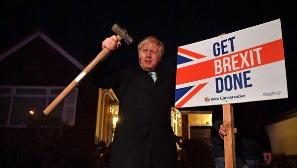 El primer ministro británico, Boris Johnson con un letrero del Brexit - Sputnik Mundo