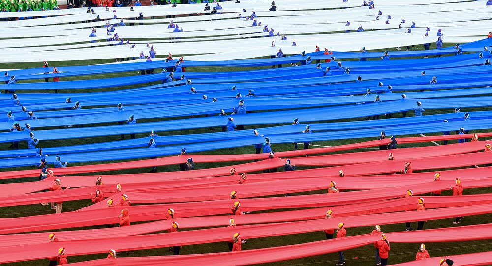 Escolares rusos apoyan los deportistas del país con una bandera de 100 metros
