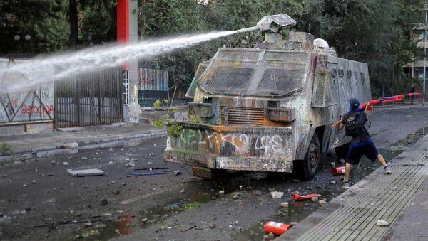 Un carro lanzaguas durante una protestas en Santiago, Chile - Sputnik Mundo