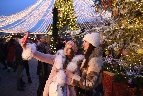 Девушки фотографируются на фестивале Путешествие в Рождество на Манежной площади в Москве - Sputnik Mundo