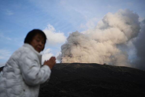 Женщина на фоне действующего вулкана в городе Асо в префектуре Кумамото - Sputnik Mundo