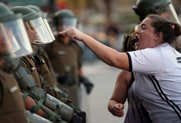 Женщина кричит на чилийских полицейских - Sputnik Mundo