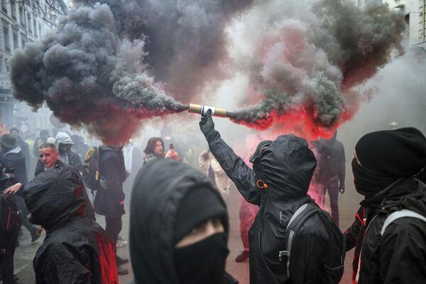 Протестующий с файером в руке во время демонстрации протеста в Лионе - Sputnik Mundo
