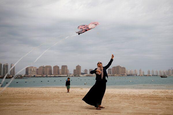 Женщина в мусульманской одежде с воздушным змеем на пляже в Дохе, Катар - Sputnik Mundo