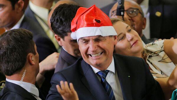 El presidente de Brasil, Jair Bolsonaro, usando un sombrero de Navidad - Sputnik Mundo