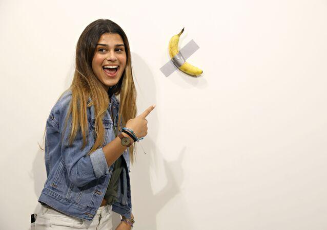 Una visitante de la exposición al lado de la obra 'Comediante' del artista italiano Maurizio Cattelan