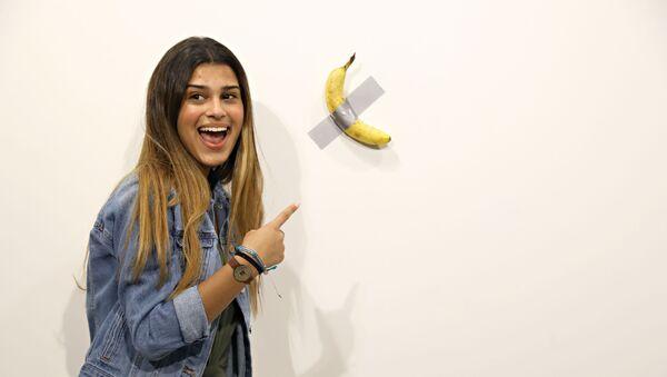 Una visitante de la exposición al lado de la obra 'Comediante' del artista italiano Maurizio Cattelan - Sputnik Mundo