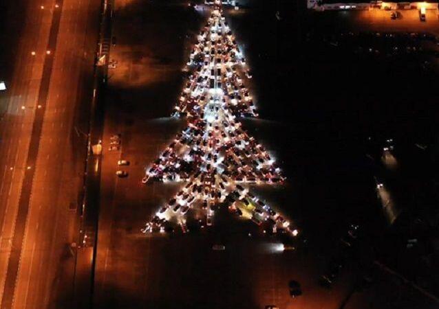 Cientos de autos forman un gigante árbol de Navidad iluminado