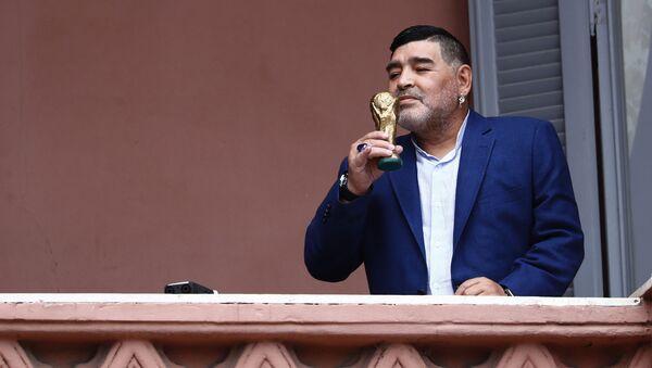 El exfutbolista Diego Armando Maradona besa una réplica de la Copa del Mundo en el balcón de la Casa Rosada - Sputnik Mundo