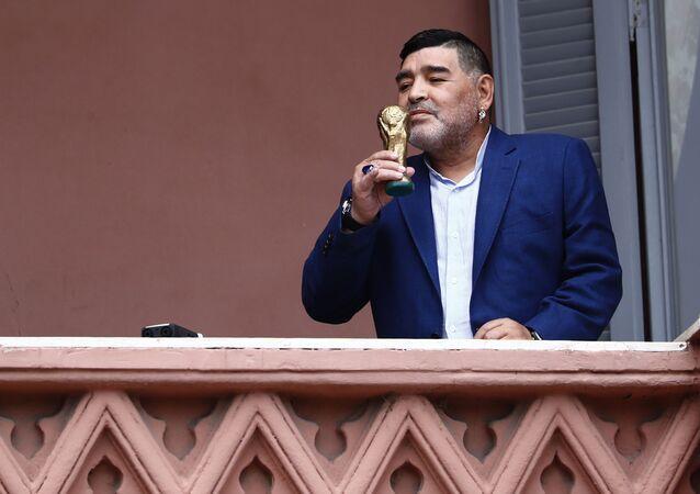 El exfutbolista Diego Armando Maradona besa una réplica de la Copa del Mundo en el balcón de la Casa Rosada