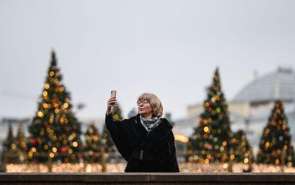 Una mujer se hace una foto con algunos de los 450 árboles decorados de la Plaza del Manege - Sputnik Mundo