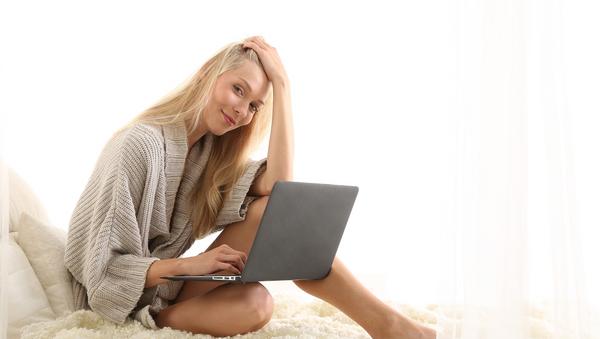 Una mujer utiliza su computadora en la cama - Sputnik Mundo