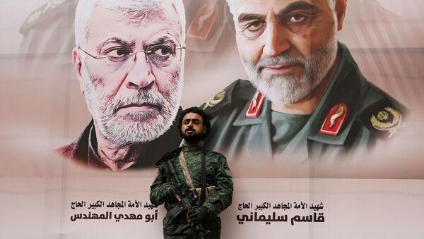 Un militar con el fondo del retrato del general Soleimani - Sputnik Mundo