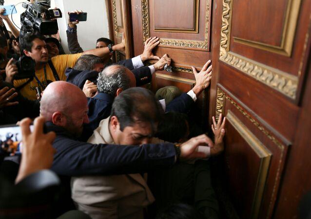 Parlamentarios venezolanos empujan una de las puertas de la Asamblea Nacional