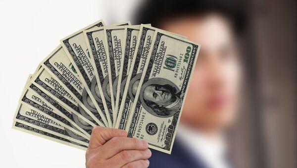 Una persona con varios billetes de cien dólares - Sputnik Mundo