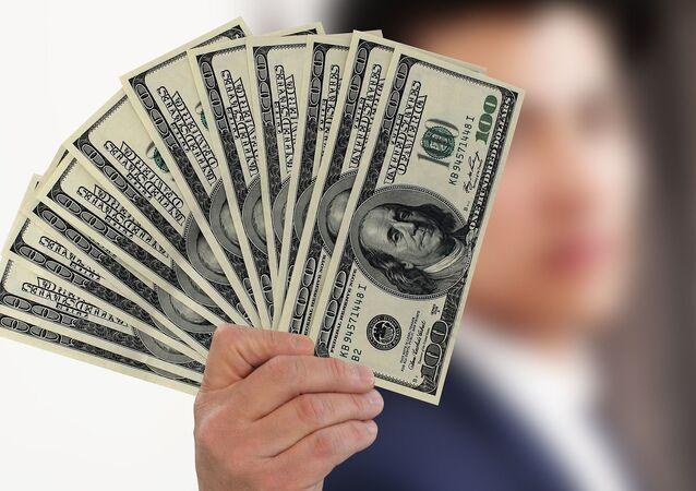 Una persona con varios billetes de cien dólares