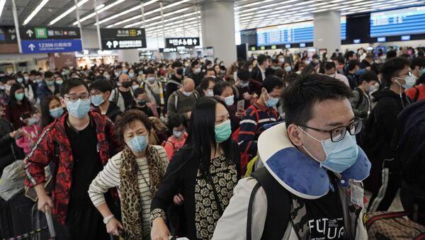Пассажиры в защитных масках на железнодорожном вокзале Гонконга - Sputnik Mundo