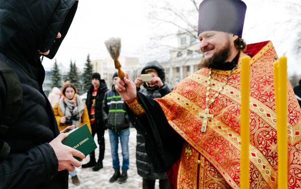 Un sacerdote bendice el boletín de notas de un universitario durante las festividades del Día de Tatiana - Sputnik Mundo
