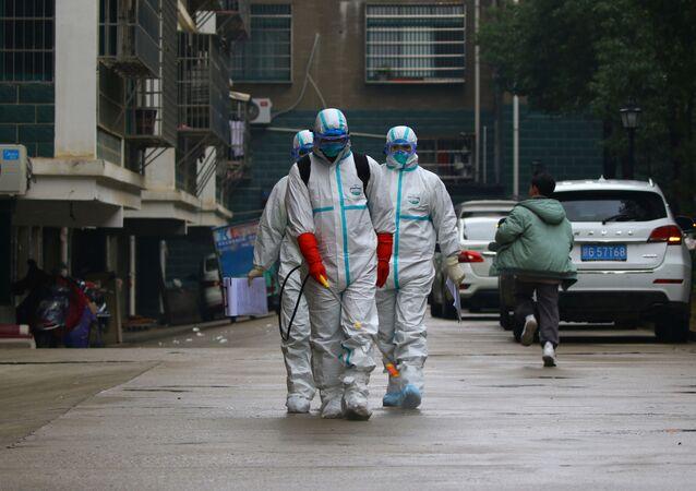 Unos trabajadores del departamento de control y prevención de enfermedades de la provincia china de Jiangxi desinfectan un área residencial después del brote de un nuevo coronavirus