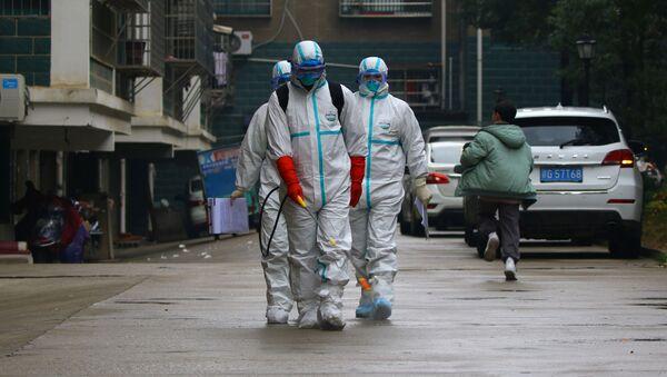 Unos trabajadores del departamento de control y prevención de enfermedades de la provincia china de Jiangxi desinfectan un área residencial después del brote de un nuevo coronavirus - Sputnik Mundo