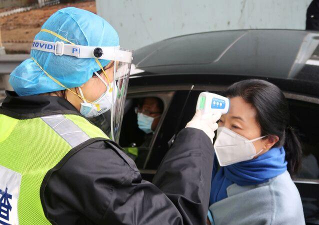 Una oficial de seguridad mide la temperatura de una mujer china