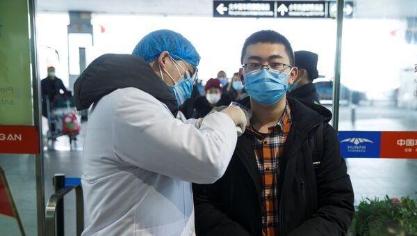 Un chino durante la revisión para detectar el coronavirus - Sputnik Mundo