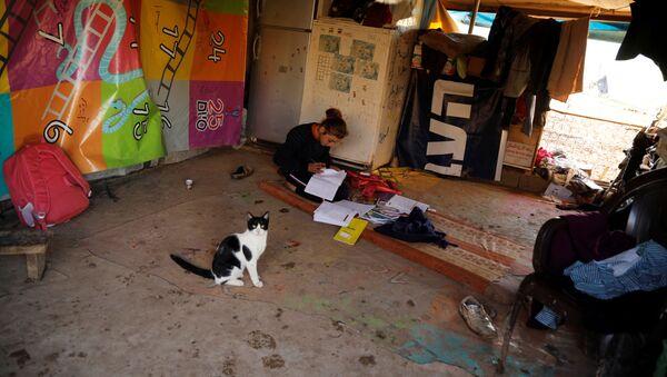 Una chica en su tienda familiar haciendo sus tareas - Sputnik Mundo